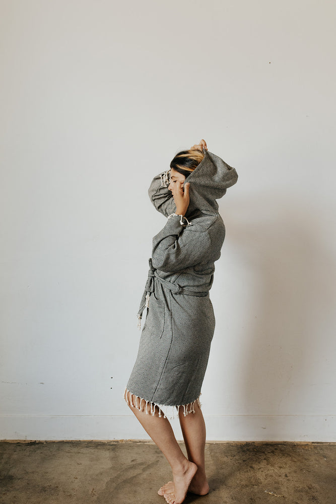 Woman wearing the Diamond Bathrobe in Charcoal with the hood up