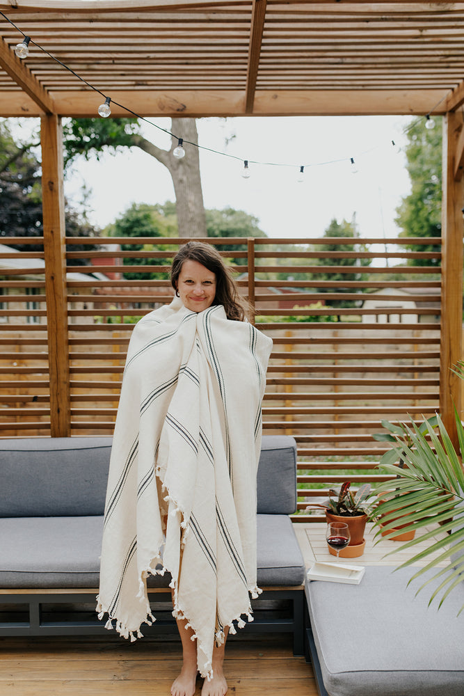Woman wrapped in the Ribbon Stripe Blanket in Pearl
