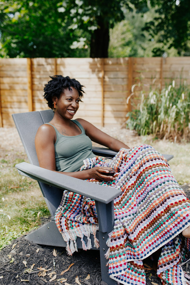 Woman sitting outside with the Rainbow Pom Pom Towel-Blanket