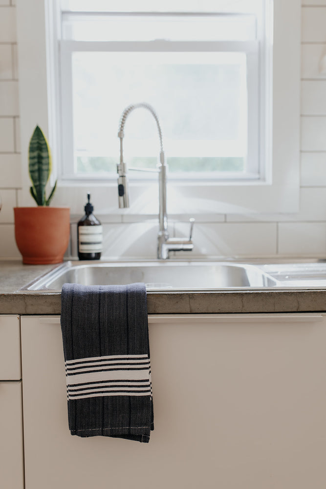 The White Stripe Hand Towel in Charcoal on the side of a kitchen sink