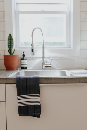 The White Stripe Hand Towel in Denim on the side of a kitchen sink