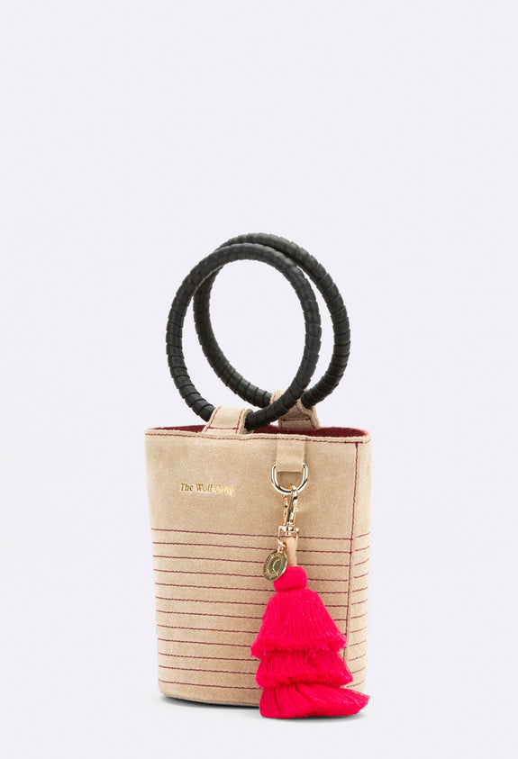 Style Odyssey The Wolf Gang is a boho girl's best friend. Inspired by exotic, far off lands, The Wolf Gang's accessories are beautifully crafted to last season after season.  Structured mini cylinder with contrast stitch detail, leather wrapped feature handles and contrast vibrant suede lining. Quality gold hardware and cotton hand-crafted tassel with custom debossed metal coin completes the style.