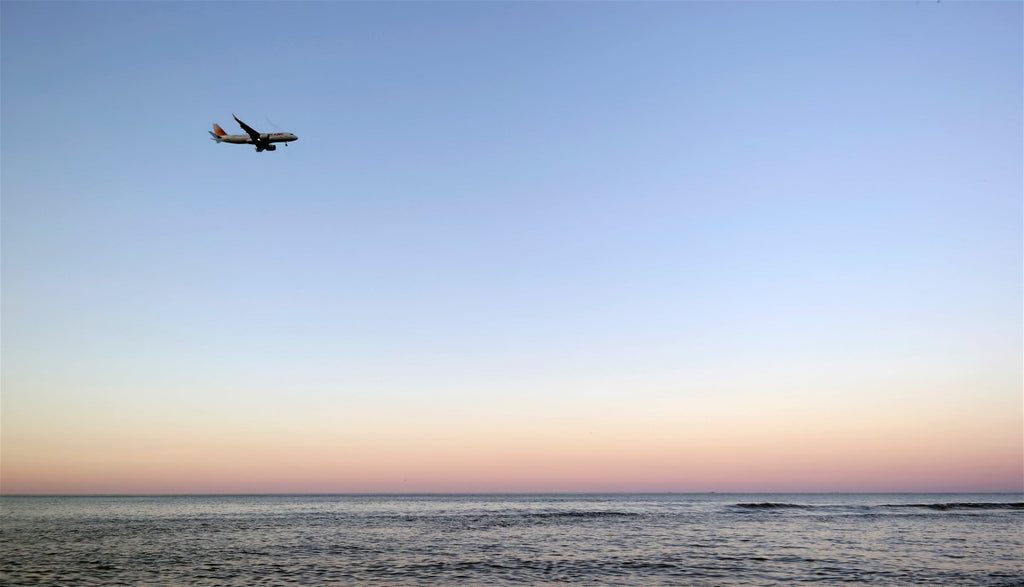 view of airplane flying in distance over a beach at sunset
