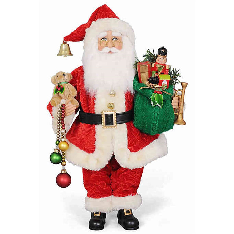 Traditional red Santa figurine carrying beaded long ornaments, a green sack of gifts and horn.
