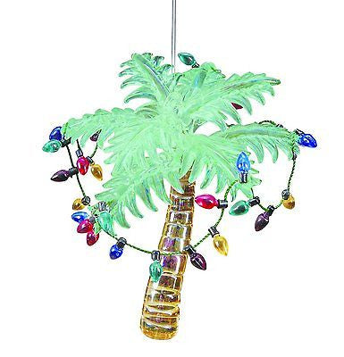 Glass palm tree ornament with green palm leaves, gold trunk & a string of multi color lights around the tree.