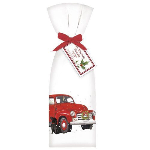 2 white towels tied with red ribbon. Towel shows a red truck in the snow and a black dog.
