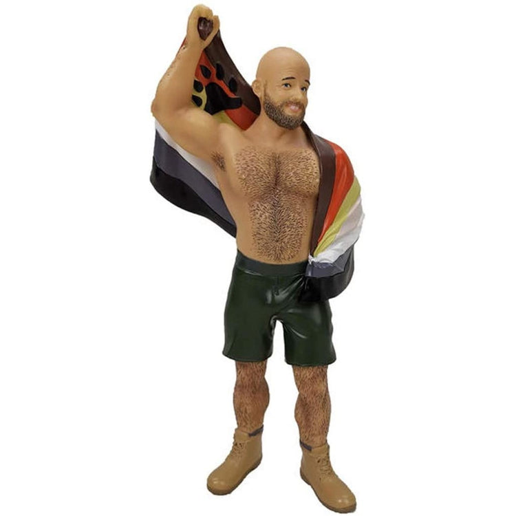 Burly man shaped figuring ornament.  Wearing black shorts, boots and carrying a pride flag.