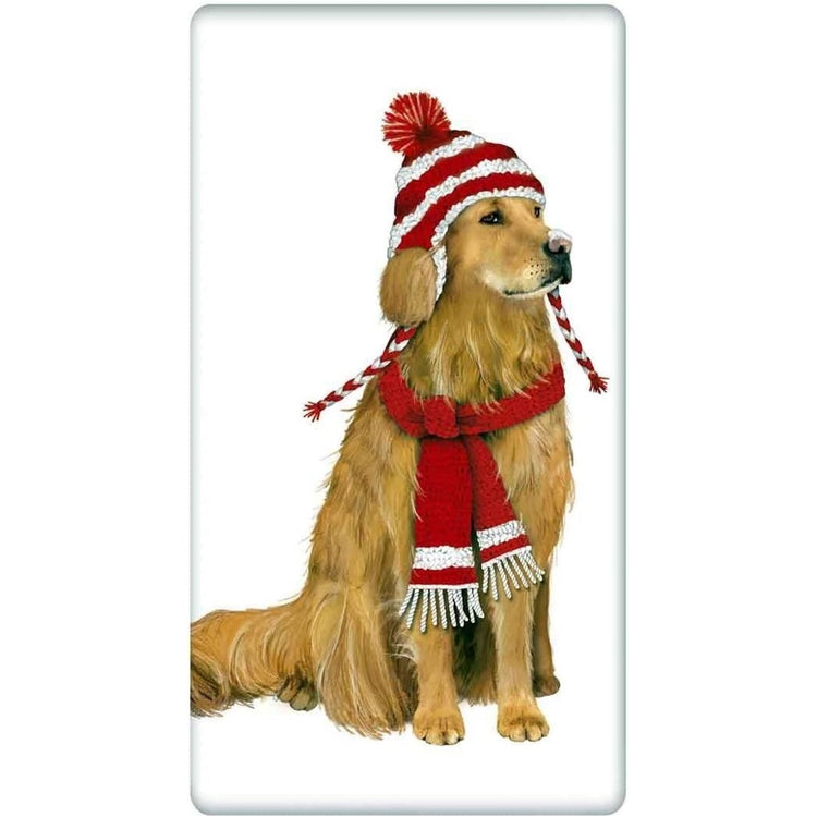 White towel. Golden retriever sits wearing red & white knit hat & scarf.
