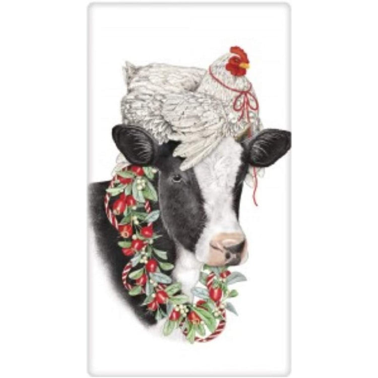 White chicken with red ribbon on a cows head with a wreath around the cows neck.