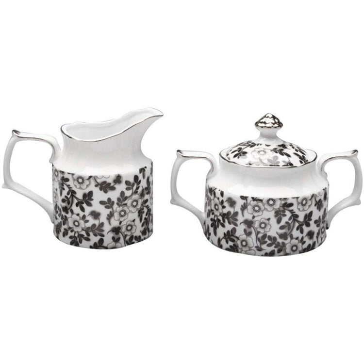 Creamer pitcher and covered sugar bowl set. The set is white porcelain with black floral design.