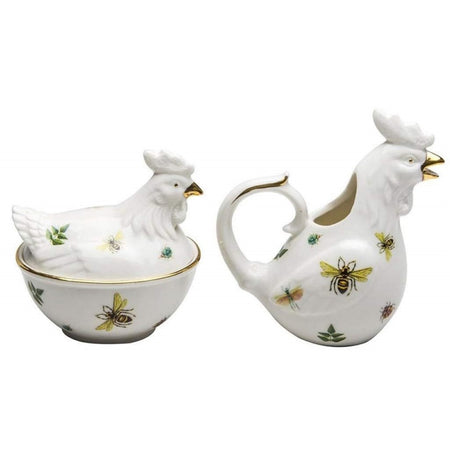 Hen shaped creamer and covered sugar bowl. White with dragonfly print and gold accents.