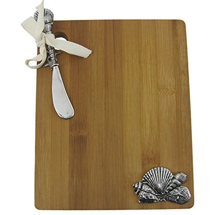 Rectangle shaped wood cutting board with silver metal seashell icons and ribbon tied shell spreader.