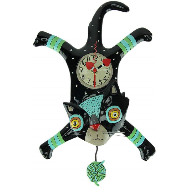 Black cat shaped clock. Cat has legs all spread out and head is down, ball of yarn pendulum.  Teal to green accents.