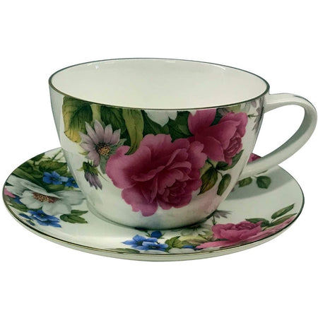 White cup and saucer with pink roses, green leaves & multi colored flowers