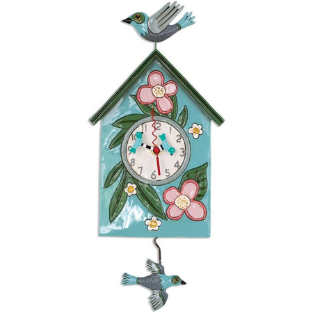 Teal birdhouse with green leaves, white & pink flowers on it. A blue bird on top & as the pendulum.