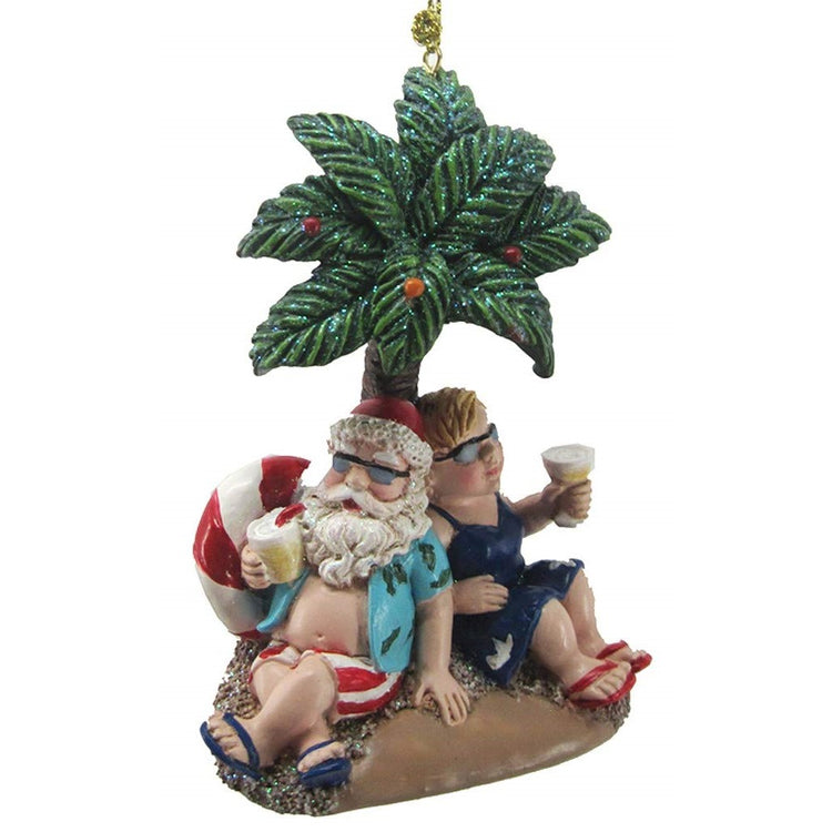 Mr. and Mr. Santa Claus under palm tree with tropical drinks figurine ornament.