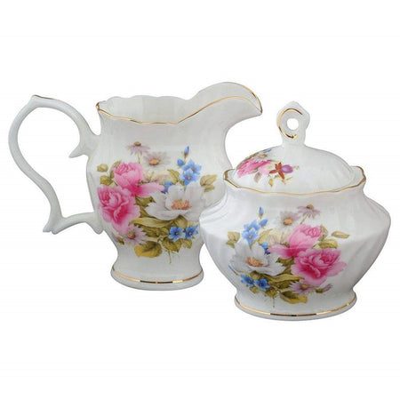 Creamer pitcher sitting next to lidded sugar bowl. . Pink, white & blue flowers on front of both & lid of sugar bowl.