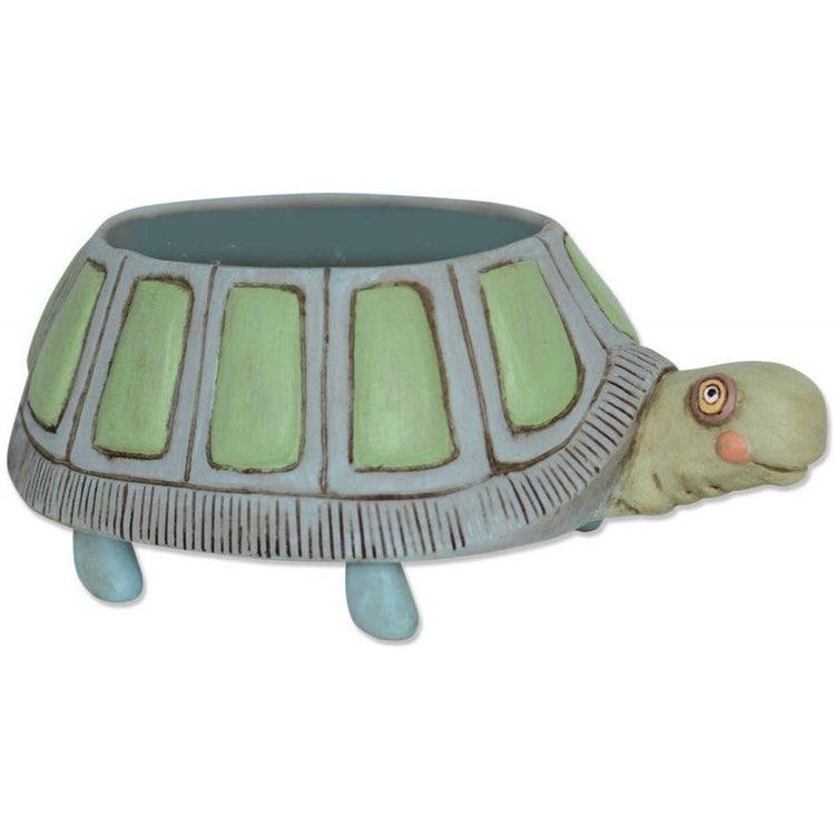 Turtle design round planter. The turtle is painted in shades of green, blue and gray. The plant sits in the shell.