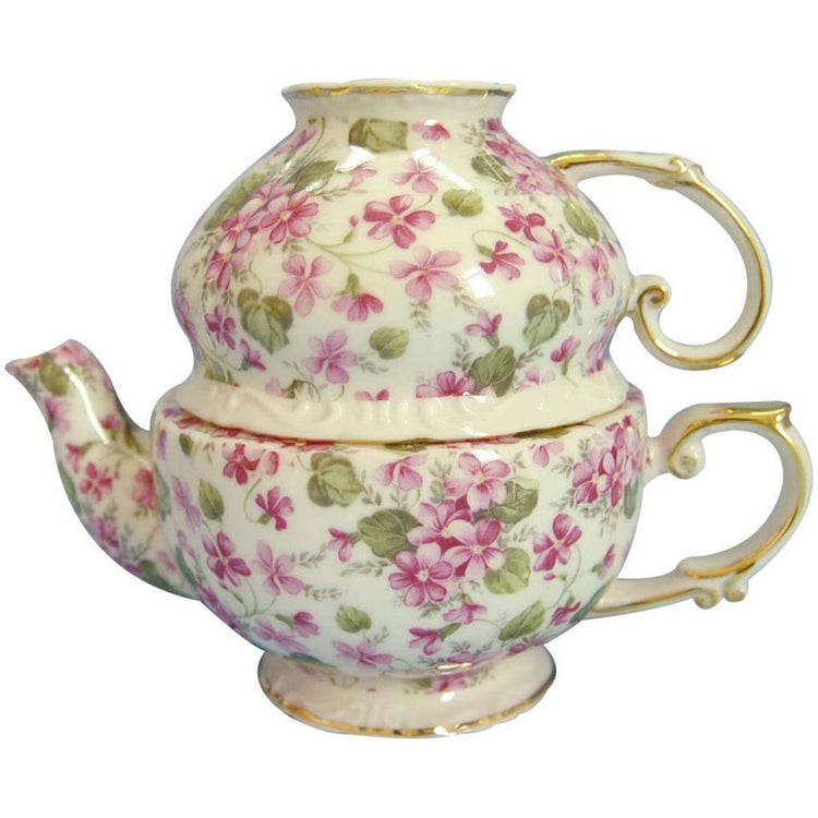 Cream colored teapot with pink flowers, green leaves, & a gold trim.