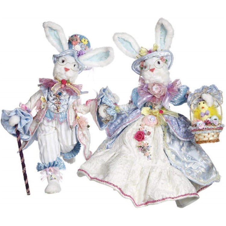2 Bunny rabbit figures with elaborate pastel blue clothing including coats, vests and hats.  Basket and cane adornments.