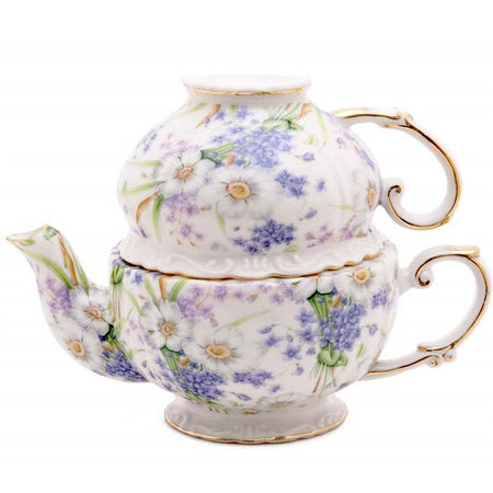 Tea for one set showing a cup upside down on top of teapot. Blue and purple floral print.