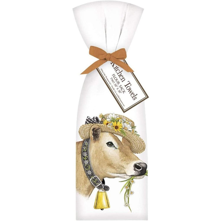 Brown cow wearing a hat and a bell, eating grass & flowers.