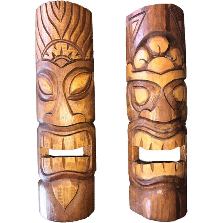 2 carved natural and stained wood tiki masks with open mouths.