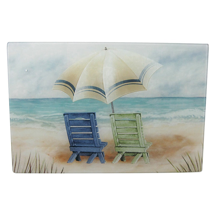 Rectangle shaped cutting board with 2 beach chairs and umbrella on beach.