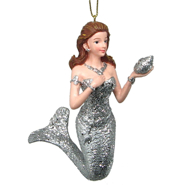 Mermaid with brown hair dressed in all sivler holding out a silver shell. Gold hanger from top.