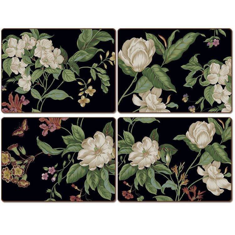 Four black placemats with white magnolias, green leaves, yellow and red accent flowers.