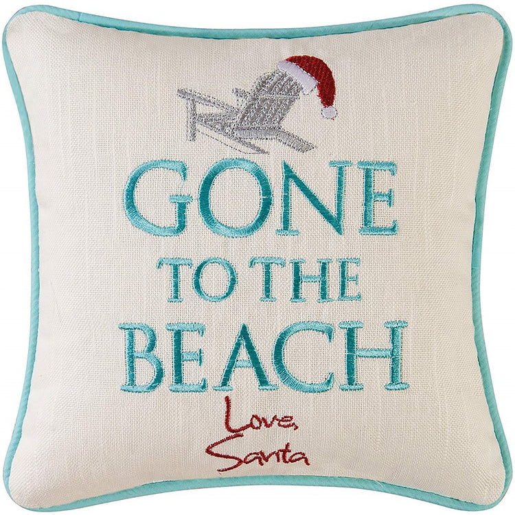 "White pillow, adirondack chair with santa hat on top. Text ""Gone to the Beach"" under that signature looking text ""Love Santa"""