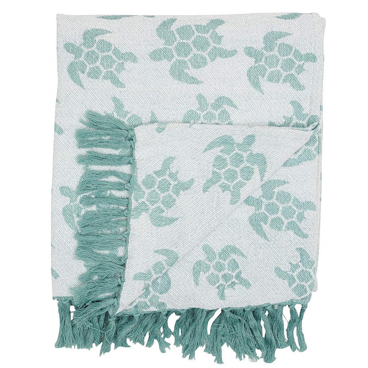 Throw blanket in shades of green with sea turtle print and fringe.