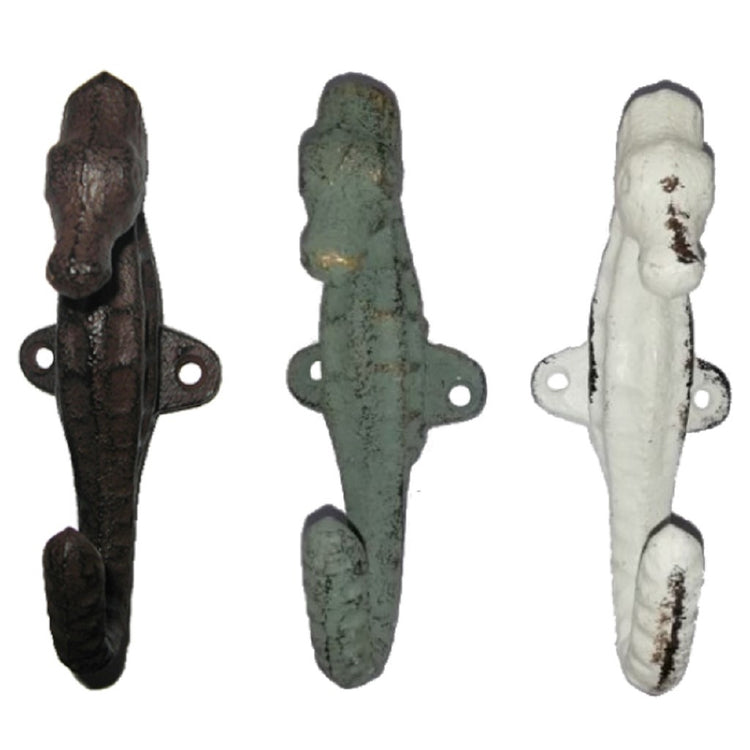3 cast iron seahorse shaped wall hooks. 1 is white, 1 is sea foam green, 1 is brown, all have a weathered look to them.