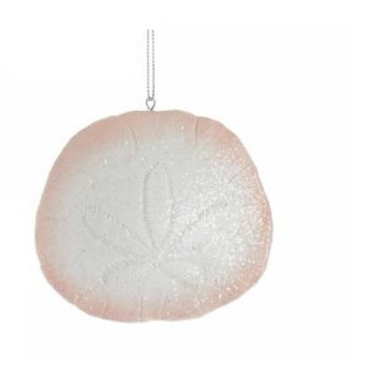 White sand dollar with a pink tint around the outside and glitter.