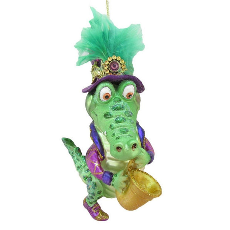 Figurine ornament shaped like an alligator blowing a saxophone.  Green hat with embellishments, purple jacket.