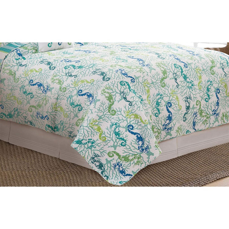 Bed with comforter. Comforter has a blue and green seahorse and coral print.