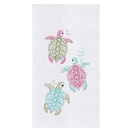 White towel with 3 baby turtle designs. 1 is pink and green, 1 is pink and blue, 1 is green and blue.