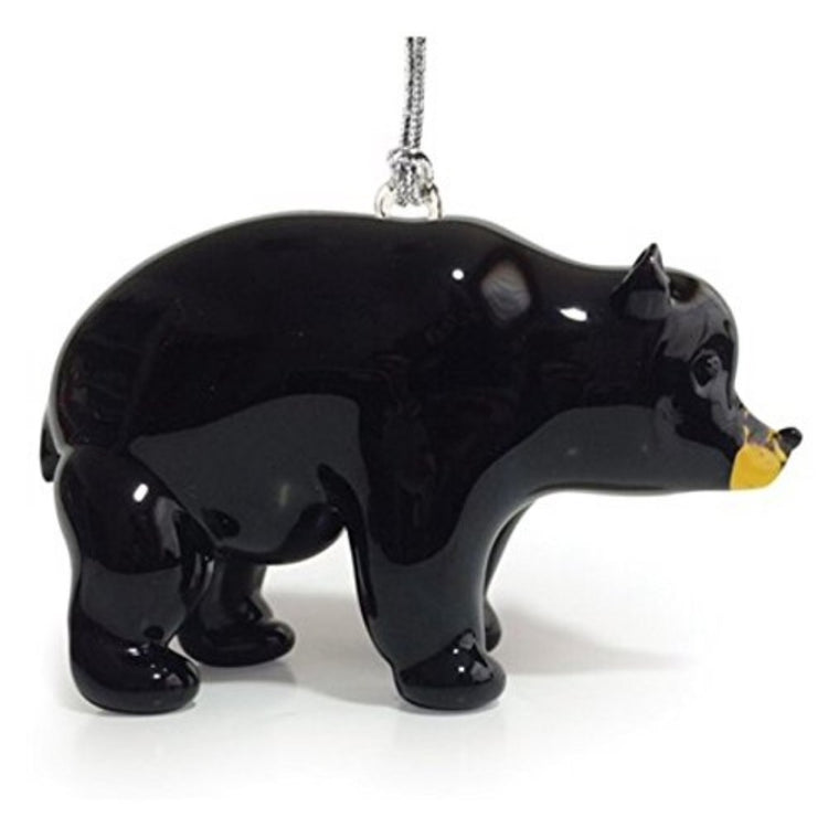Glass bear ornament standing on all 4 feet. Bear is black except for yellow around snout & mouth. Hanger attached to back.