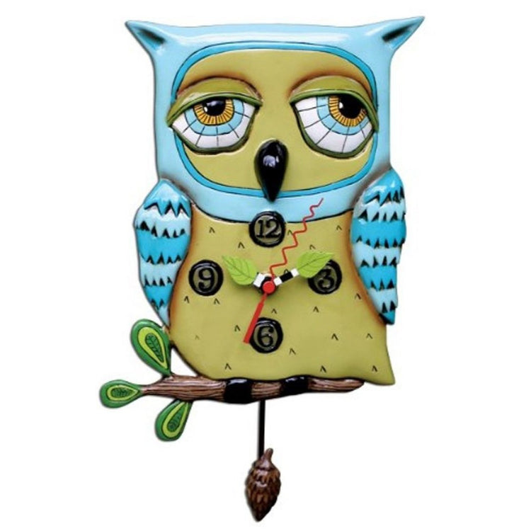 Blue and yellow owl shaped clock. Owl is sitting on a brown branch with a pinecone shaped pendulum.