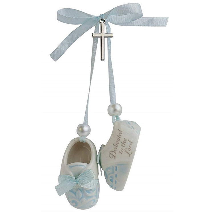 "Pair of blue baby shoes with metal cross and blue ribbon. ""Dedicated to the Lord"" print on side."