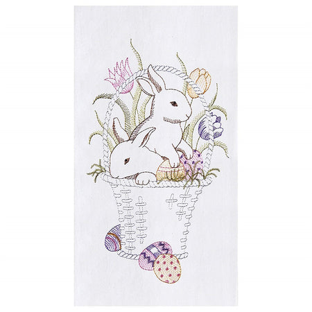 White flour sack kitchen towel embroidered with bunnies in a basket.