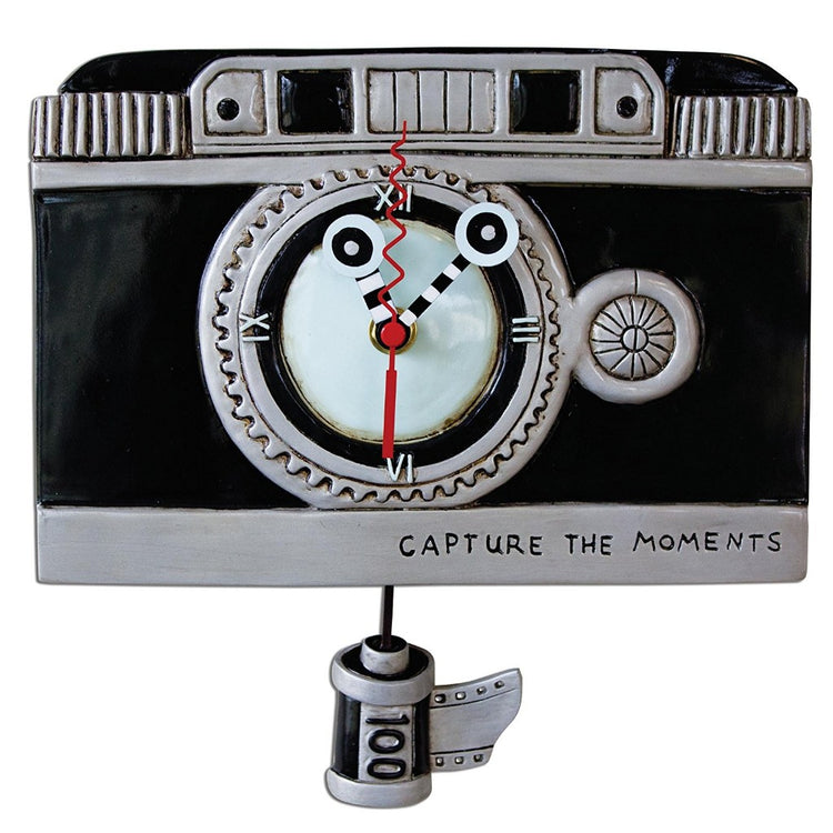 Black and silver clock that replicates a camera with a roll of film shaped pendulum