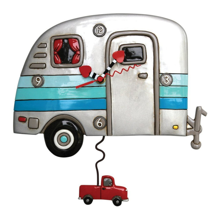 Pull camper shaped clock with truck pendulum underneath. Camper is silver with 3 blue stripes. hands are red, black & white.