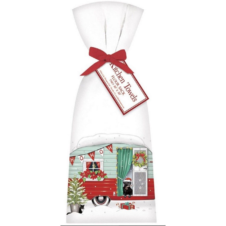 2 white towels tied with a red ribbon. Towel shows a green and red vintage camper, a black dog, and a fir tree in the snow.