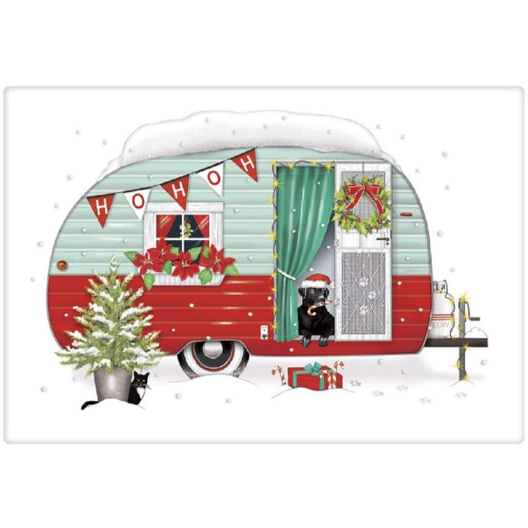 White dishtowel with red and green camper.  Black lab dog wearing a Santa hat sits in doorway.  It is snowing.