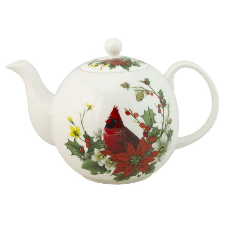 White teapot with red cardinal sitting in greenery.