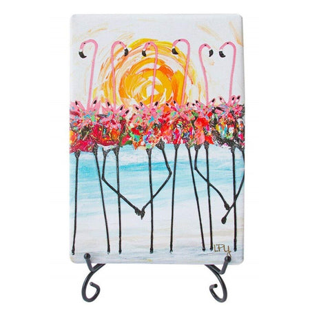 White canvas rectangle print on black wire stand. 6 Pink flamingos wearing colorful tutu's in front of sun.
