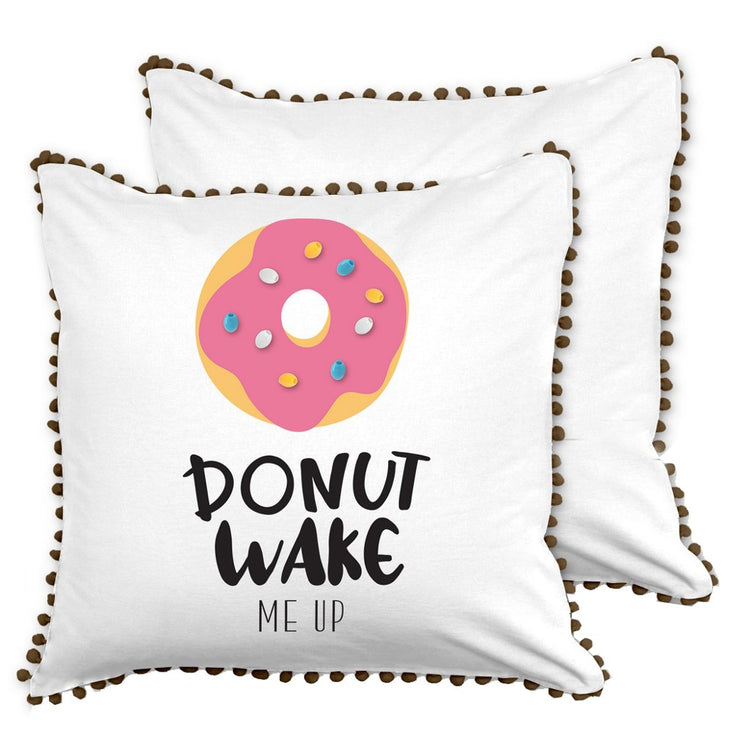 "Square white pillow with black fringe, donut design on front "" DONUT WAKE ME UP""."
