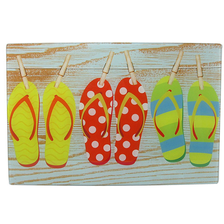 Rectangle shaped cutting board printed to look like 3 pairs of flip flops on laundry line in front of wood.