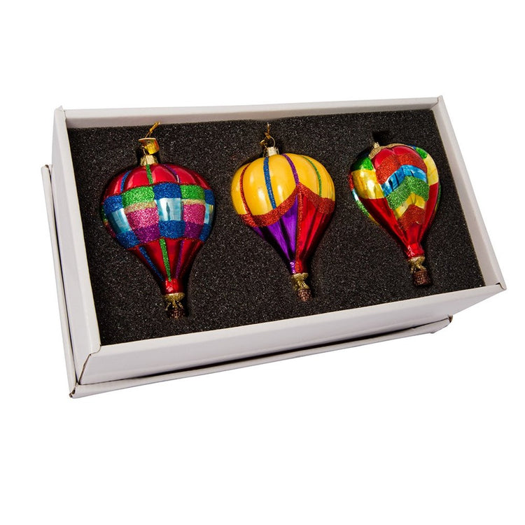 3 blown glass hot air balloon ornaments in a black and gold box. All are rainbow colored with a variety of patterns.